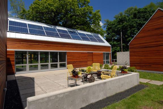 In this image the sun control doors are open to allow the sun to penetrate and warm the house.  The PV's on the roof power the net zero energy use house